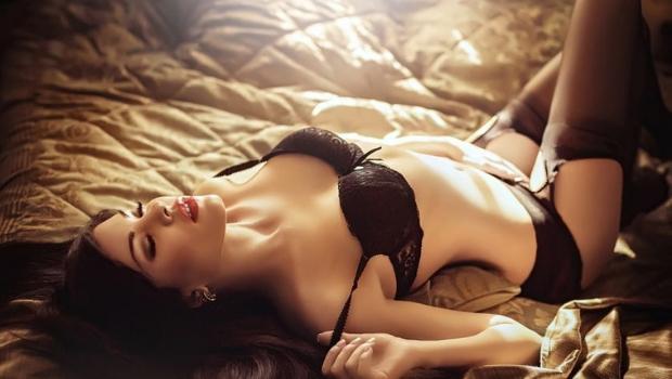 Hübsche Serbin liegt in Spitzenunterwäsche auf einem Bett